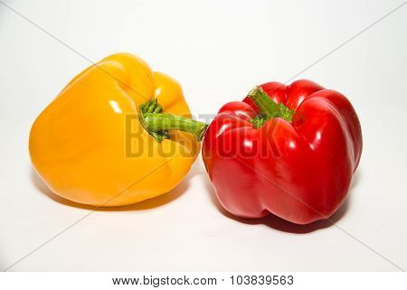 Two Ripe Red And Yellow Peppers On Over White