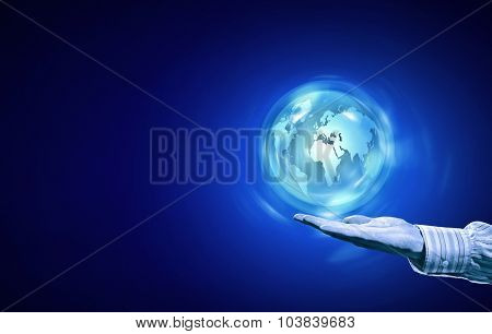 Person hand and digital Earth planet on palm on blue background