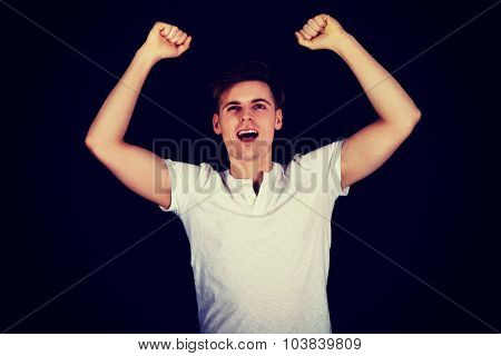Young happy man with hands up in a winner gesture.