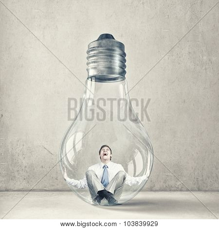 Screaming businessman trapped inside of light bulb