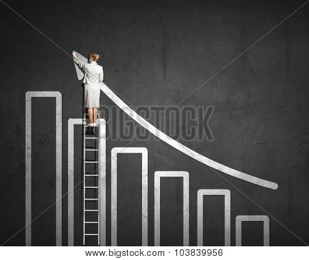 Rear view of businesswoman standing on ladder and touching top of arrow