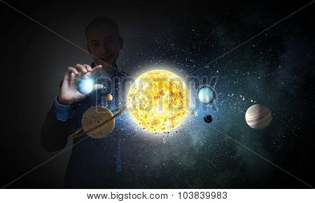 Young businessman taking with fingers planet of sun system