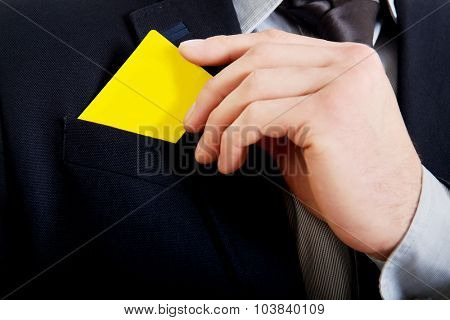 Businessman taking his yellow personal card from pocket.