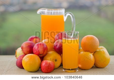 orange juice and lots of fruits on wooden table outdoor