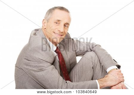 Side view happy businessman sitting on the floor.