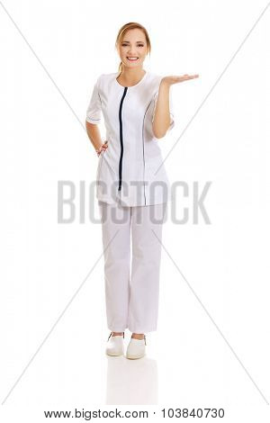 Young happy female doctor holding abstract space on palm.