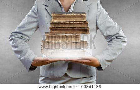 Close up of businesswoman holding pile of books in hands
