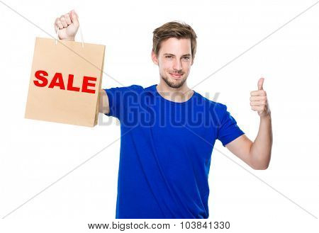 Man with shopping bag and thumb up and showing a word sale