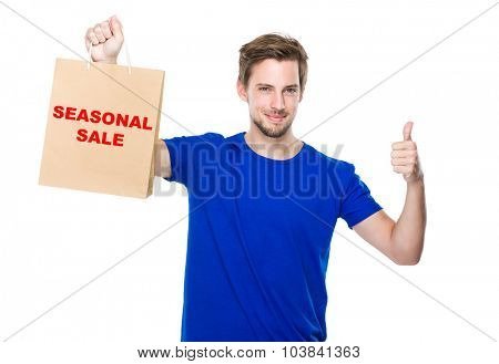 Man with shopping bag and thumb up and showing phrase of seasonal sale