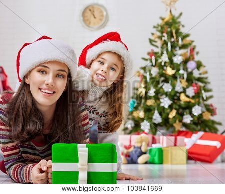 Child with mother playing near Christmas tree