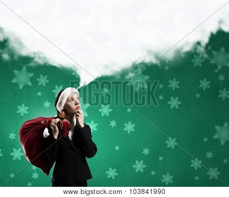 Thoughtful Santa woman with red gift bag on back