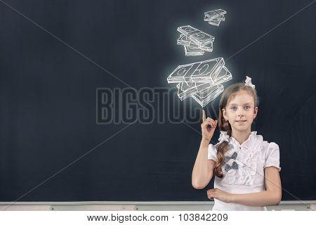 Cute school girl pointing at money drawn on blackboard