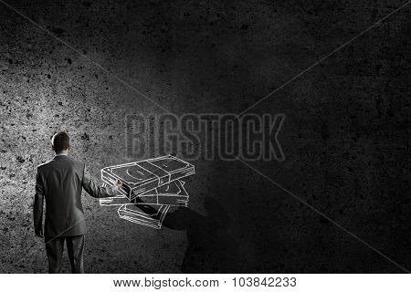 Back view of businessman drawing money banknotes on wall