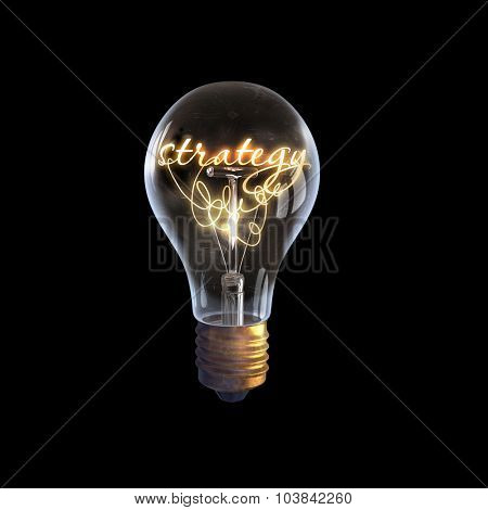 Glowing glass light bulb with strategy word inside