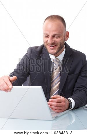 Happy businessman shutting down laptop computer, sitting at desk.