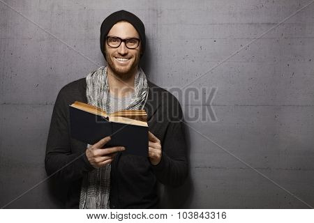 Happy urban style young man standing against grey wall, smiling, reading book, looking at camera.