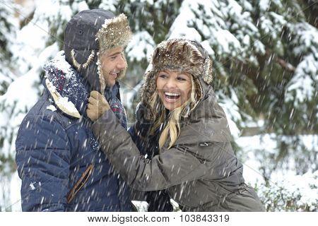Happy loving couple having winter fun in snowfall.