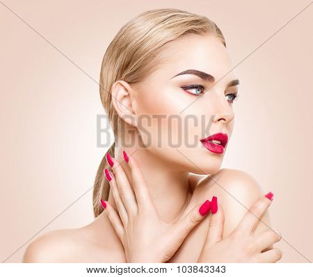 Beautiful fashion model woman with perfect makeup, red lips and nails, blond hair. Red lipstick and manicure. Portrait of glamour girl with bright makeup over beige background. Beauty female face