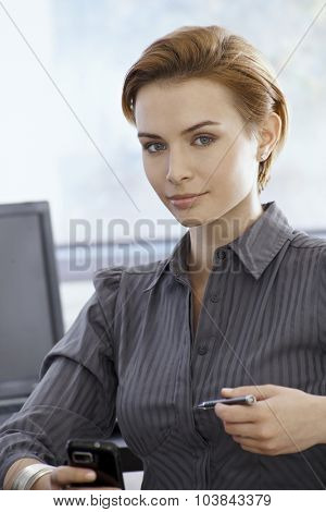 Portrait of attractive young businesswoman holding mobilephone, looking at camera.