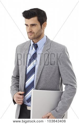 Handsome young businessman walking with laptop computer in hand, looking away.
