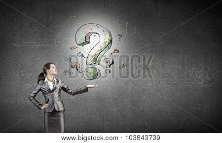 Young businesswoman holding question mark in palm