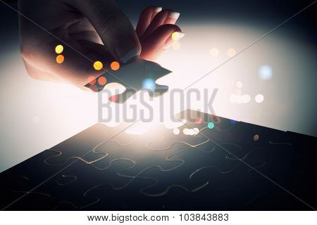 Hand connecting missing jigsaw glowing puzzle piece