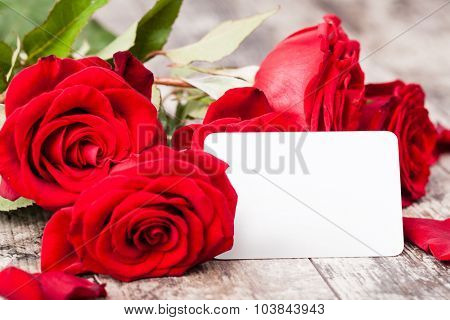 Red roses with a blank gift tag on a woodwn