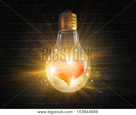 Glowing light bulb and red heart inside of it