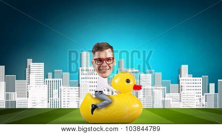 Young happy businessman riding yellow rubber duck