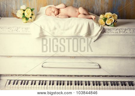Little newborn baby sleeps on a white piano. Vintage style. Music, art concept.