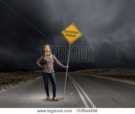 Young woman satnding on road with signboard