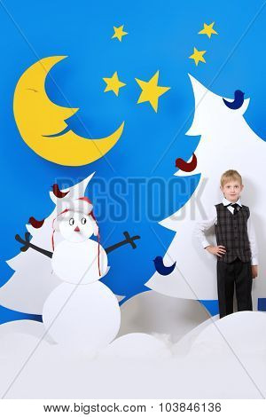 Cheerful boy in a cartoon fairy snowy forest. The magic of Christmas night. Full length portrait.
