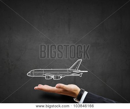 Close up of businessman hand holding drawn airplane