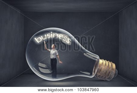 Young businesswoman inside of glass light bulb
