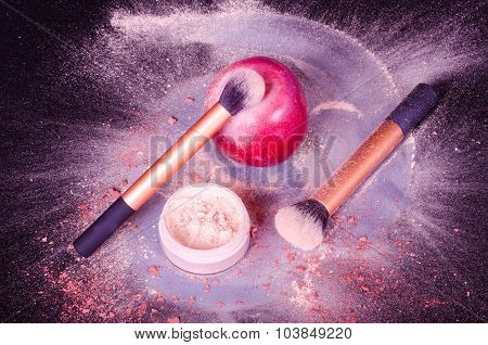 Face powder, two brushes, and red apple on black