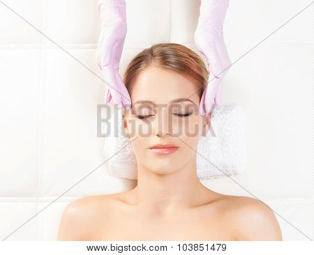 Young attractive woman getting massaging treatment over white background