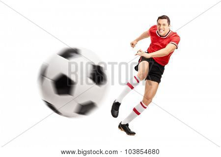 Young football player kicking a ball hard isolated on white background with the focus on the player