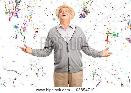 Joyful senior gentleman standing in a bunch of confetti streamers isolated on white background