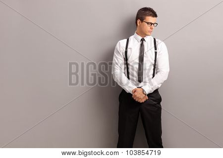 Elegant young man standing against a gray wall and looking to the side