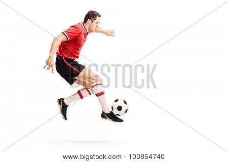 Profile shot of a young athlete in a red jersey jumping and kicking a football isolated on white background