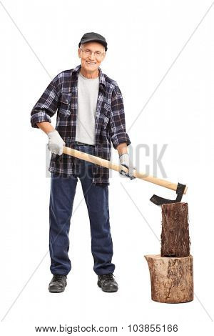 Full length portrait of a senior man in a checkered shirt splitting a log with an axe isolated on white background