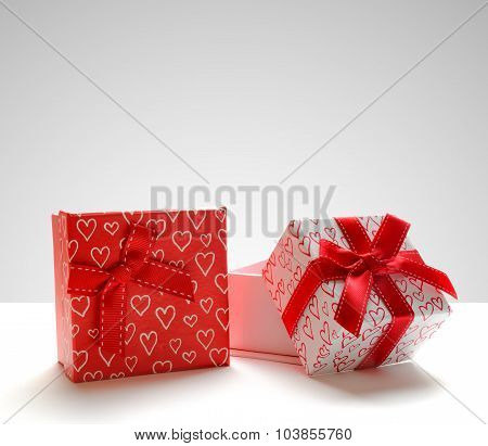 Two Gift Boxes With Hearts Printed Standing Grey Background Front