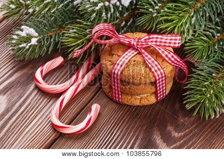Christmas gingerbread cookies, candy cane and tree branch on wooden table