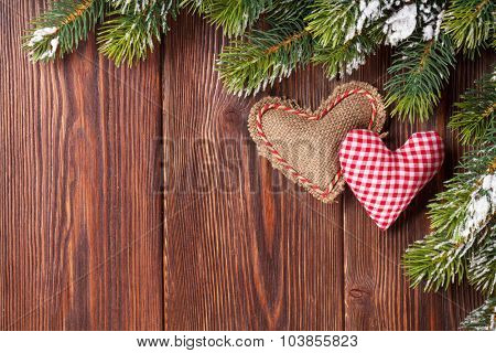 Christmas tree branch with snow and heart toys on wooden table. Top view with copy space