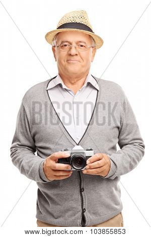 Vertical shot of a senior gentleman holding a camera and smiling isolated on white background