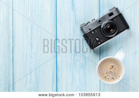 Travel camera and coffee cup on wooden table. Top view with copy space