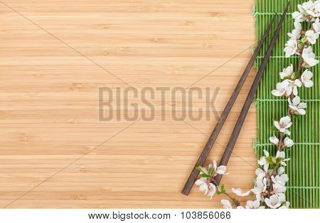 Chopsticks and sakura branch over bamboo mat with copy space