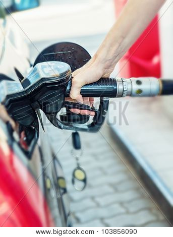 Pretty young woman refuel the car detail photo