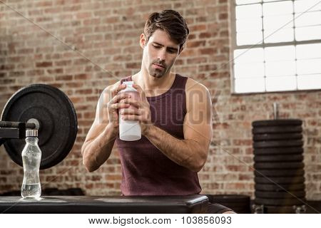 Man shaking shaker bottle at the gym