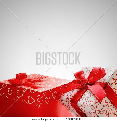 Two Gift Boxes With Hearts Printed With Grey Background Closeup